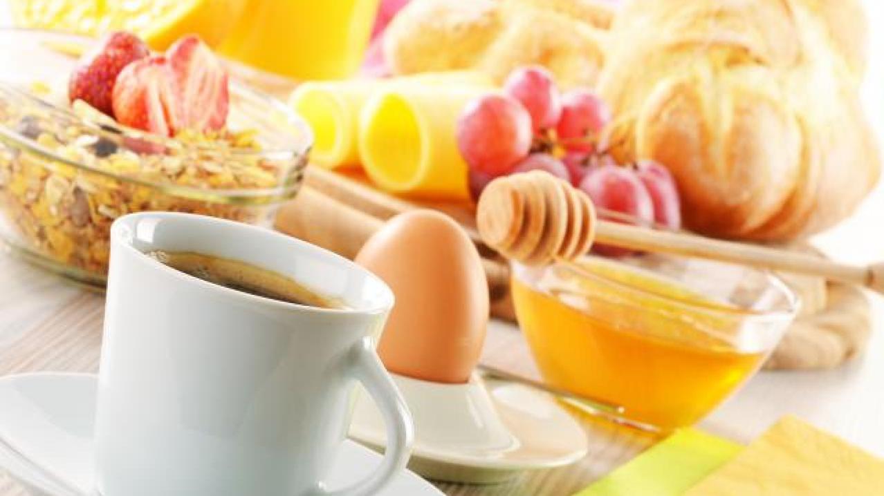 Aliments du petit déjeuner, incluant un café, des céréales, des fruits, un croissant et du miel.