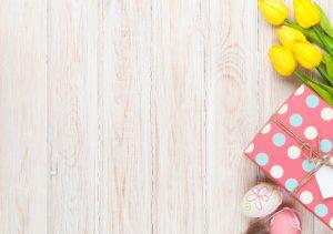 Deux oeufs décorés, des tulipes jaunes et un cadeau enveloppé